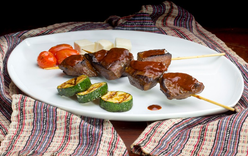 Anticuchos de corazón accompanied by sauteed vegetables.
